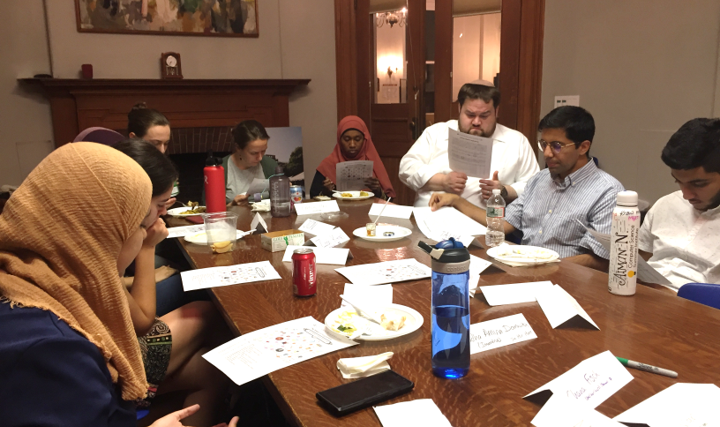 Students of different faiths gathered around a table reading text at the Multi-faith salon at Earl.